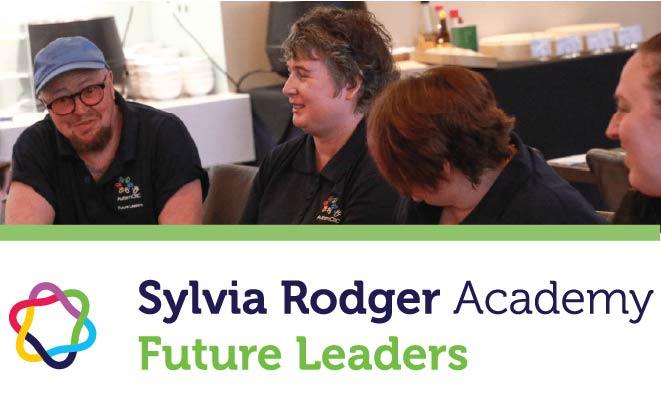 """Photograph of people in a conference room smiling. Text"""" Sylvia Rodger Academy - Future Leaders"""