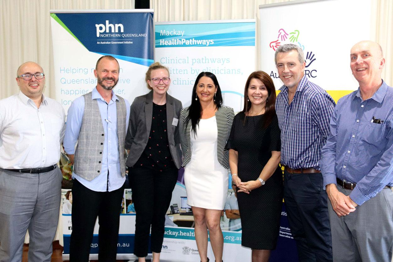 Seven people stand in in front of banners for phn Norther Queensland, Mackay HealthyPathways and AutismCRC